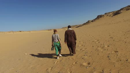 aswan : ASWAN, EGYPT - FEBRUARY 7, 2016: Back view of nubian man wearing traditional clothing walking in desert with female tourist.