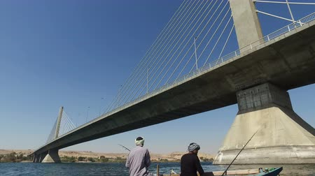 aswan : NILE, EGYPT - FEBRUARY 8, 2016: Two local man fishing on Nile under Aswan bridge Stock Footage