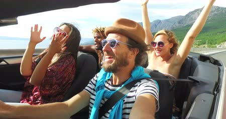 śpiew : Bearded hipster man with a hat driving and singing with his friends in convertible car