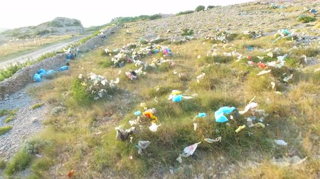 plastics : Aerial view of plastic bags lying in grass by asphalted road, Pag island, Croatia Stock Footage