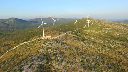 dozen : Flying above elegant ecological wind turbines on green sunny hills Stock Footage
