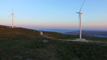 dozen : Flying above two elegant ecological wind turbines on sunny hill path