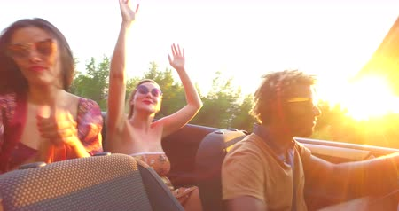 hipster : Young party people dancing to music while driving fast in convertible at sunset