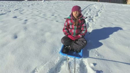 luge : Little girl on sledge on snowly hill in sports jacket Stock Footage