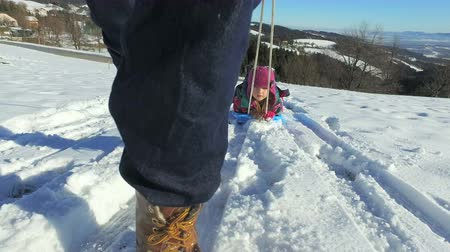 luge : Father pulling daughter on sledge on snowly hill on sunny day