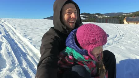 luge : Father and daughter on sledge on snowly hill on sunny day Stock Footage