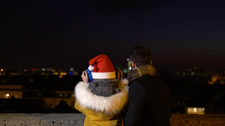 Father and daughter using pay binoculars at Christmas market, Zagreb, Croatia.