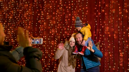 Mother taking photo of family at Christmas market on the night.