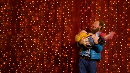 Father holding son in front of lights wall at Christmas market.