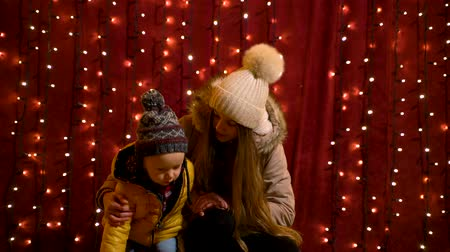 Two teenager posing and waving in front of lights wall at Christmas market. Wideo