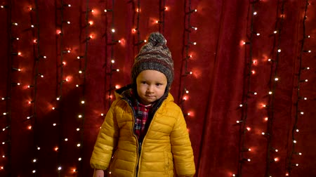 Young boy posing serious in front of lights wall at Christmas market. Wideo