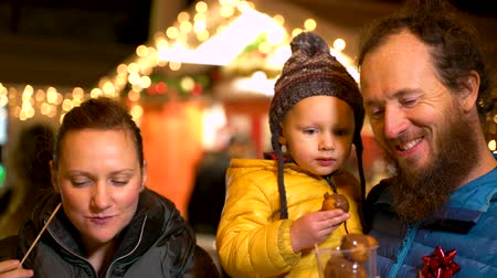 Couple and son enjoying traditional drink at Christmas market, Zagreb, Croatia.