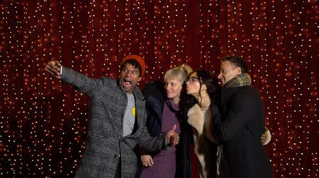 African american taking selfie with friends in front of light wall at Christmas market. Wideo