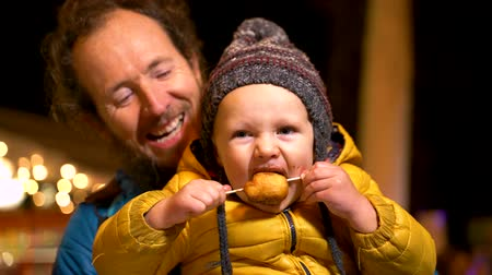 Portrait of father holding son at Christmas market in Zagreb, Croatia.