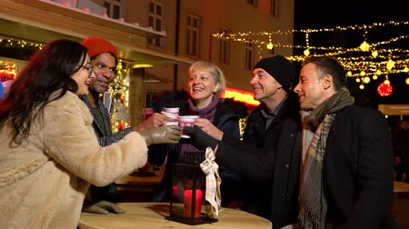 mulled wine : Group of friends chating at Christmas market, Zagreb, Croatia. Stock Footage