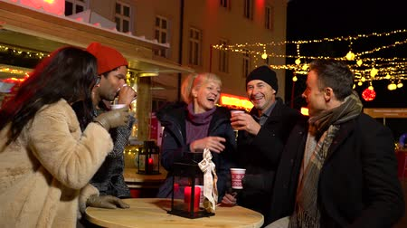 mulled wine : Group of friends laughing and cheering with traditional drink at Christmas market, Zagreb, Croatia.