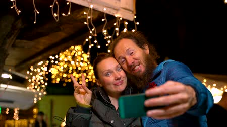 Couple taking selfie at traditional Christmas market, Zagreb, Croatia.