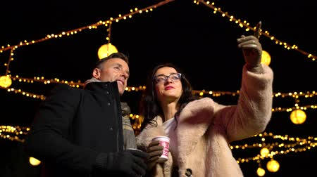mulled wine : Couple pointing to decoration at Christmas market. Zagreb, Croatia.