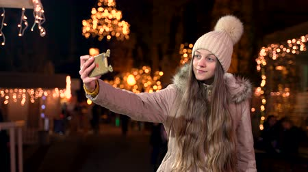 Beautiful teenager with long hair taking a selfie at Christmas market. Wideo