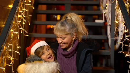 Mother kissing cheek of daughter at Christmas market, Zagreb, Croatia.