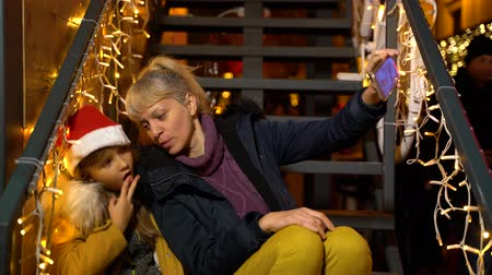 Mother talking selfie with daughter at Christmas market, Zagreb, Croatia. Wideo
