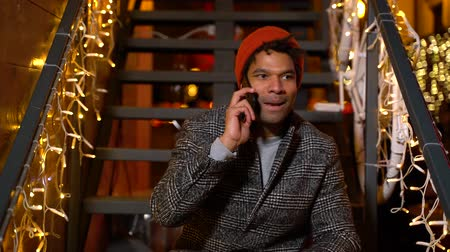 enfeite de natal : African american man talking on cell phone at Christmas market, Zagreb, Croatia. Stock Footage