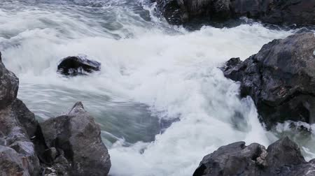 water running down a wild river stones