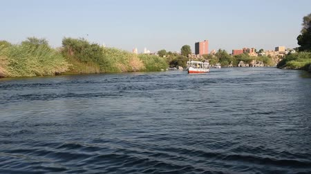 aswan : Sailing down large wide river Nile in Aswan Egypt through rural countryside landscape with rocky cataract islands and mountain background Stock Footage