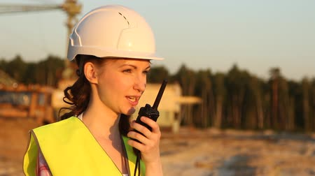 the conception : Pretty woman in helmet discusses something by walkie talkie with huge excavator on background Stock Footage