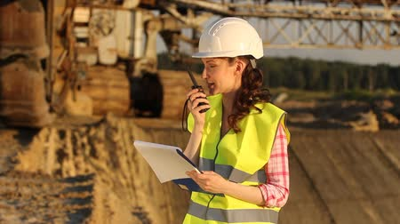 védősisak : attractive woman communicates on a building site by cb radio
