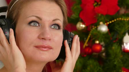головной убор : Beautiful adult woman listening music against Christmas tree