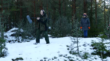 fur headphones : JAN 15, 2015 HOUTSKARI, FINLAND: Film crew. Soundman worker with headphone holding a telescopic microphone. Steps sound recording.