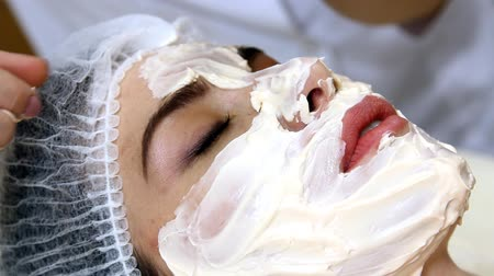 towel : Applying facial mask at woman face at beauty salon