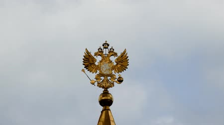 scepter : JUN 10, 2015 MOSCOW Russian coat of arms - two-headed eagle with scepter and orb on the background of running clouds. The coat of arms is crowned with the crown of the Izmailovo Kremlin. Time lapse.