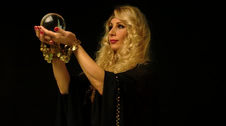 astrologer : Beautiful blond astrologer woman looking through a crystal ball. Fortune telling.