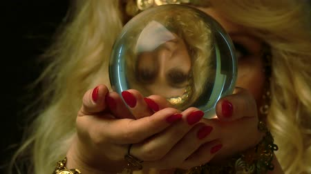 astrologer : Female fortune teller is looking in the future through crystal ball. Close up view.