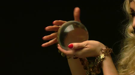 Female fortune teller is looking in the future through crystal ball. Close up view.