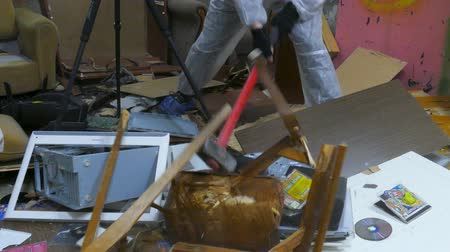 marreta : APR 04, 2018 MOSCOW, RUSSIA: The man destroys an old chair by a sledgehammer in the ruins of an apartment Vídeos
