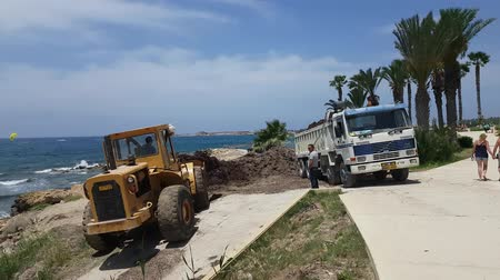 buldozer : MAY 22, 2018, LARNACA, CYPRUS: Removal of seaweed ejected by the ocean from the beach, Paphos, Cyprus