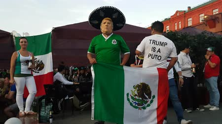 politika : JUN 16, 2018 MOSCOW, RUSSIA: Mexican soccer funs with national flag and Trump is a Puto sign on T-shirt