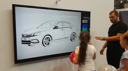 history : A girl paints LADA car on an interactive whiteboard at Moscow Automobile Salon. SEP 03, 2018 MOSCOW, RUSSIA Stock Footage