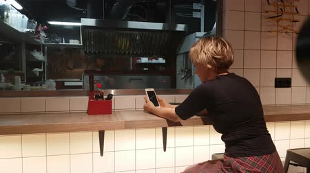 Woman with mobile phone waiting her food in front of glass in chinesian Wok cafe.