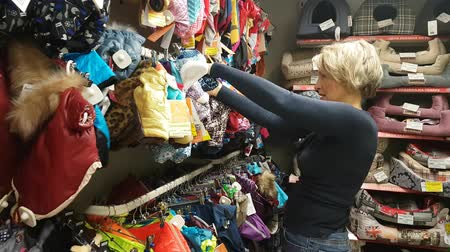 The girl chooses clothes for a dog in a pet store. NOW 24, 2018 MOSCOW, RUSSIA