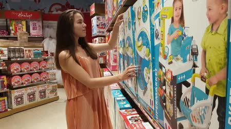 кукла : Pretty girl in state Childrens world store choosing the doll. MAY 15, 2018 MOSCOW, RUSSIA Стоковые видеозаписи