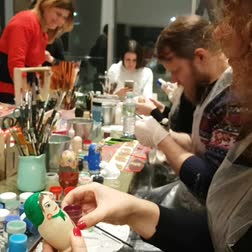 Group of people paints dolls, traditional Russian wooden toys. DEC 18, 2018 MOSCOW, RUSSIA Dostupné videozáznamy