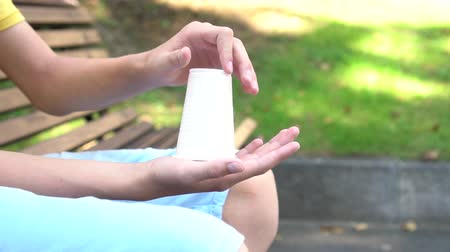 újrahasznosított : A teenager breaks a white plastic cup with both hands. The concept of not using plastic to save the ecology of the planet, slow motion Stock mozgókép