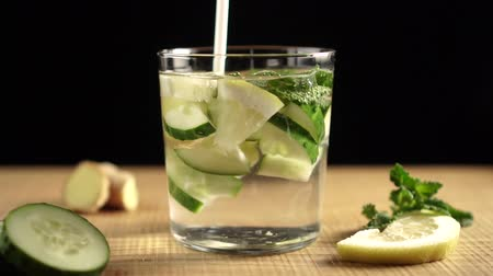 sassy : Stir the white plastic straw of the Sassi cocktail ingredients in a glass. Water, lemon, cucumber, imbar, mint. Sassi for weight loss. Stock Footage