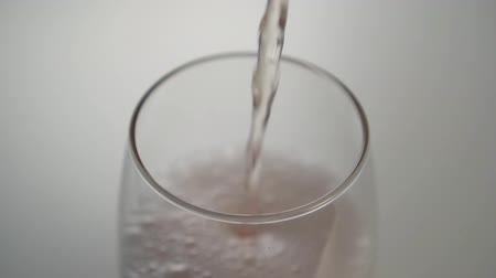 efervescente : A soft stream of frothy drink falls into a glass beaker. Slow filling of bubbling liquid
