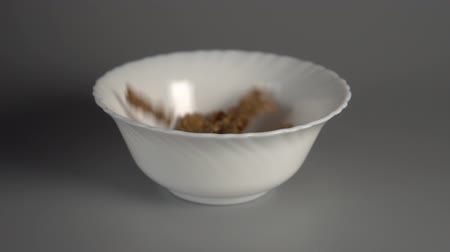 oat flakes : Oatmeal slowly fall into a white plate on a gray background. Healthy breakfast concept. Slow motion Stock Footage