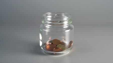 горсть : Coins cents fall into a jar of savings and overshoot, bouncing off the edge of the tank. The concept of accumulating money for paying taxes and loans. slow motion. slow motion